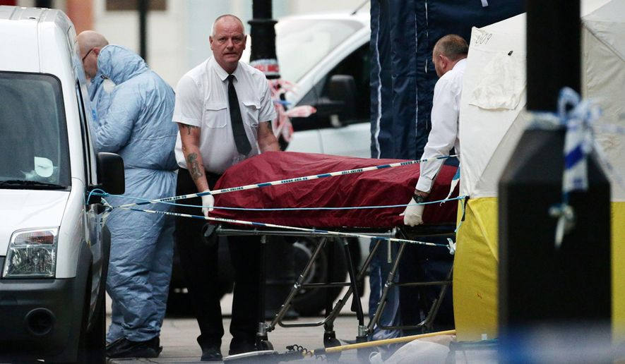 A body is removed from the scene in Russell Square, central London, after a knife attack Thursday, Aug. 4, 2016. A woman has died and others were injured in a knife attack in a central part of London, the police said Thursday. (Yui Mok/PA via AP)