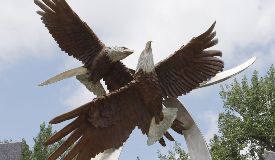 The twin bald eagle statue in Founders Park in Rapid City, SD, honors fallen Rapid City Police officers Ryan McCandless and Nick Armstrong, who were shot and killed on duty five years ago.  (Chris Huberl/Rapid City Journal via AP)