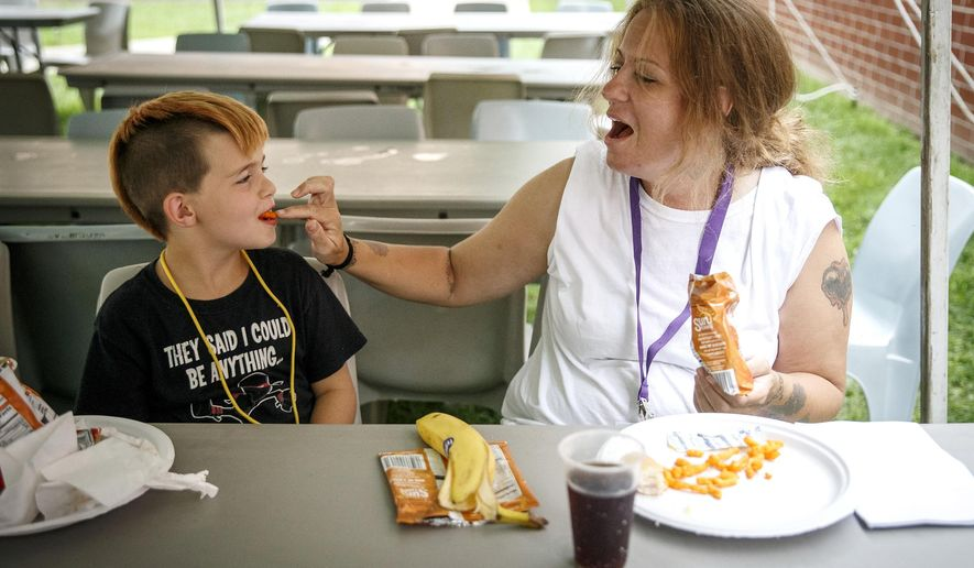 In this Aug. 2, 2016 photo, Amanda Taylor, right, serves up Cheetos to her 7-year-old son, Wesley, as they spend their lunch together during the Mom and Me camp at the Logan Correctional Center, in Lincoln, Ill. Participants in the three day camp get to spend eight hours with their mothers during the day at the prison and then go back to a campground in Bloomington for the nights where they get to forge bonds with other children in the same situation. (Justin L. Fowler /The State Journal-Register via AP) NO SALES, MANDATORY CREDIT