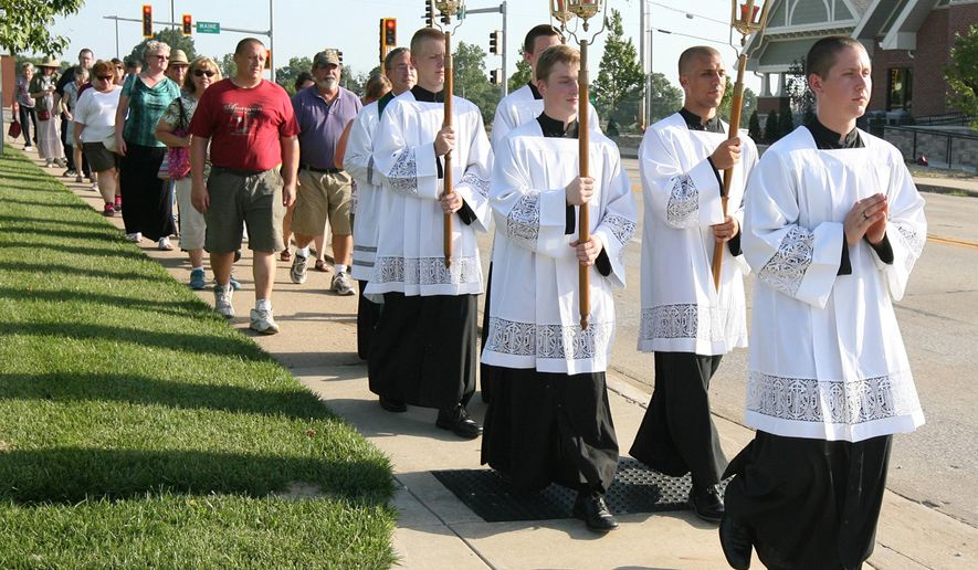 In this July 17, 2016 photo, a group of servants lead a procession in Quincy, Ill., to mark the 130th anniversary of Father Augustus Tolton's return to the city after his studies and ordination in Rome. When the Rev. Tolton returned to Quincy in 1886, hundreds of Quincyans welcomed home the country's first recognized black priest with open arms. This years celebration, a much smaller, but no less reverent, crowd marked the anniversary with prayer and a procession to St. Peter Catholic Cemetery, where Tolton has been buried for almost 120 years. (Alyse Thompson/The Quincy Herald-Whig via AP)