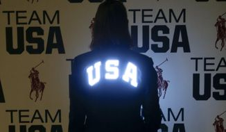 In this July 25, 2016 photo, Olympian Kelly Hurley models a custom-fitted Polo Ralph Lauren jacket at the United States Olympic Committee processing station in Houston that features electroluminescent panels illuminating the US Olympic team symbol and the lettering on the back of the jacket, which swimmer Michael Phelps will wear as he takes his spot in the opening ceremony as the country's flag bearer.  (AP Photo/Bob Levey)