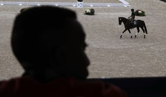 A man watches as riders practice on their horses at the Olympic Equestrian Center ahead of the 2016 Summer Olympics in Rio de Janeiro, Brazil, Thursday, Aug. 4, 2016. (AP Photo/John Locher)