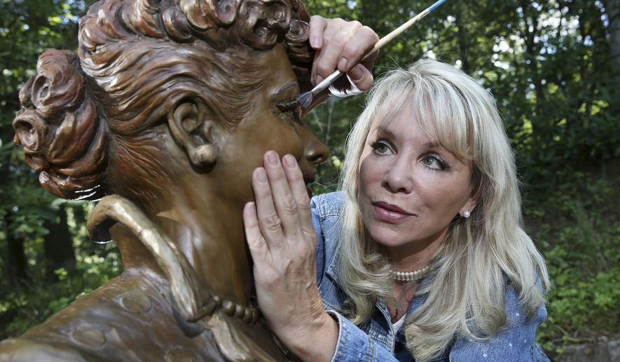 """In this Wednesday, July 20, 2016 photo, artist Carolyn Palmer prepares to apply a cold patina to her bronze statue of Lucille Ball in Saddle River, N.J. The sculptor was chosen to create a replacement statue for one dubbed """"Scary Lucy,"""" in the late actress Ball's hometown. The much-maligned statue of Ball will be replaced after it drew worldwide attention as """"Scary Lucy,"""" according to the mayor of the western New York village where the 1950s sitcom actress and comedian grew up and her life-size bronze has stood since 2009. (AP Photo/Mel Evans)"""