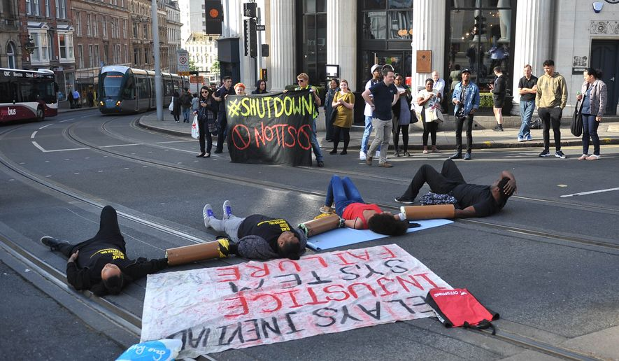 Activists lay on the road outside Nottingham Theatre Royal as they attempt toshut down part of the city centre tram and bus network in Nottingham, England Friday Aug. 5, 2016 to protest for social justice movement Black Lives Matter. Activists affiliated with the U.S.-based group Black Lives Matter have blocked a road leading to Heathrow Airport, and Nottinghamand city centre and in other British cities (Edward Smith/PA via AP)
