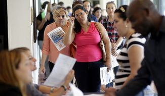 In this Tuesday, July 19, 2016, photo, Reina Borges, left, stands in line to apply for a job with Aldi at a job fair in Miami Lakes, Fla. On Friday, Aug. 5, the Labor Department issues its jobs report for July. (AP Photo/Lynne Sladky)