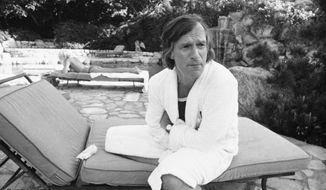 Hugh Hefner, lounging in the backyard of his 30-room Los Angeles mansion, tells a reporter the Playboy Company is being forced into more efficient and economic operation on Aug. 4, 1975. (Associated Press) **FILE**