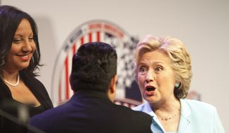 Democratic presidential candidate Hillary Clinton is welcomed by National Association of Black Journalists (NABJ) President Sarah Glover, left, and National Association of Hispanic Journalists (NAHJ) President Mekahlo Medina at the 2016 (NABJ)/ (NAHJ) joint convention, Friday, Aug. 5, 2016, in Washington. (AP Photo/Paul Holston)