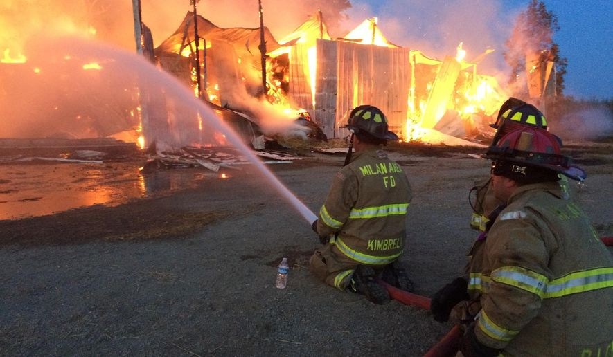 Firefighters work to extinguish fire that destroyed a barn containing thousands of bales of hay on Thursday, Aug. 4, 2016, in Monroe County's Dundee Township, Mich. Dozens of firefighters from several departments fought the blaze at the metal-sided barn, which is located in a wooded area. (Ray Kisonas/The Monroe News via AP) MANDATORY CREDIT