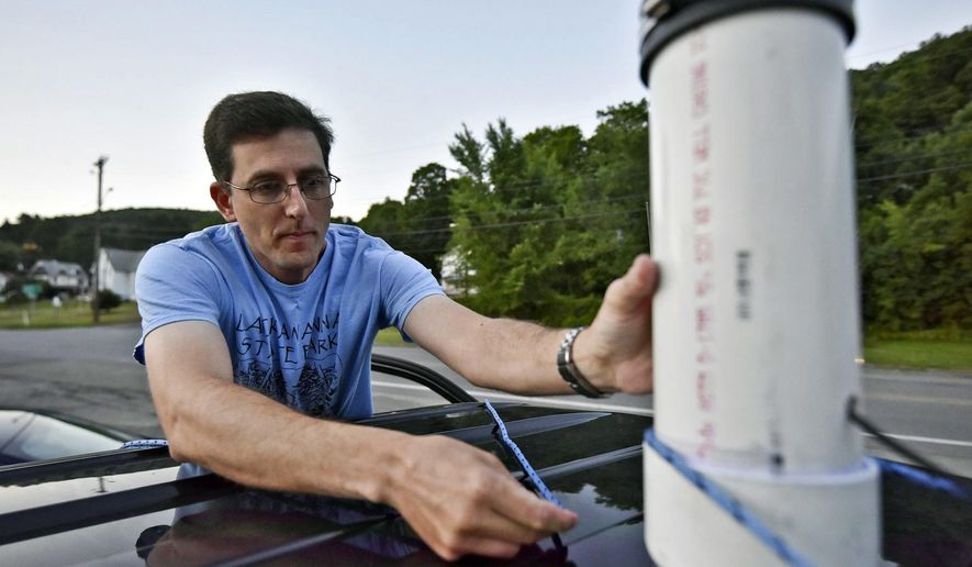 This photo taken July 20, 2016, shows Rich Fritsky, a wildlife diversity biologist for the Pennsylvania Game Commission, setting up a high-tech microphone on the roof of his vehicle that can detect the sound of bats in Hop Bottom, Pa. (Jason Farmer /The Citizens' Voice via AP)