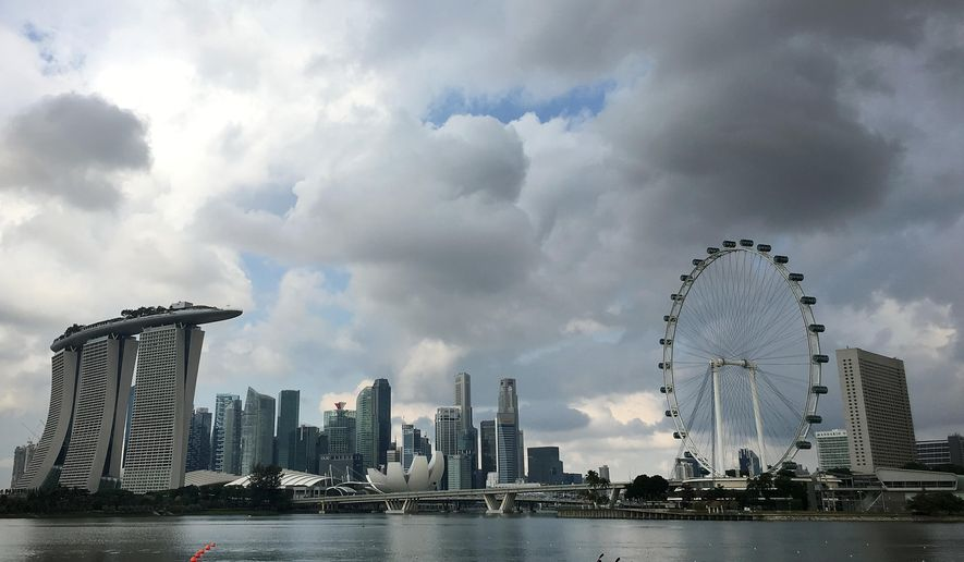 FILE - In this Wednesday, April 20, 2016, file photo, two kayaks are dwarfed against the skyline of the Marina Bay area, which is home to popular hotels, and tourist attractions such as the Singapore Flyer, the city-state's observation wheel seen at right, in Singapore. Indonesia's counter-terrorism police on Friday arrested six suspected militants who were allegedly planning to launch a rocket attack on Singapore's downtown from nearby Batam island. (AP Photo/Wong Maye-E, File)