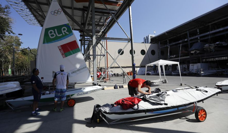 Team members and athletes work on their boats at the Marina da Gloria Sailing venue, ahead of the 2016 Summer Olympics opening ceremony in Rio de Janeiro, Brazil, Friday, Aug. 5, 2016. (AP Photo/Gregorio Borgia)