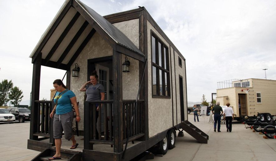 In this July 16, 2016, photo, Brynna Brockback, left, and Leslie Kay, right, exit a model tiny house at a display outside the Cabela's in Lehi, Utah. The Tiny Home movement is a worldwide change in the way people use their living spaces. The Daily Herald reports it is becoming a trend in Utah County. (Chris Samuels/The Daily Herald via AP)