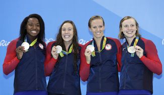 From left, Simone Manuel, Abbey Weitzeil, Dana Vollmer and Katie Ledecky from the United States show off their silver medals during the ceremony for the women's 4x100-meter freestyle final during the swimming competitions at the 2016 Summer Olympics, Saturday, Aug. 6, 2016, in Rio de Janeiro, Brazil. (AP Photo/Michael Sohn)