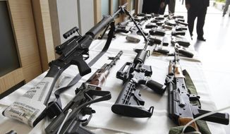 Various guns are displayed at the Chicago FBI office in this July 22, 2010, file photo. (AP Photo/M. Spencer Green, File) **FILE**