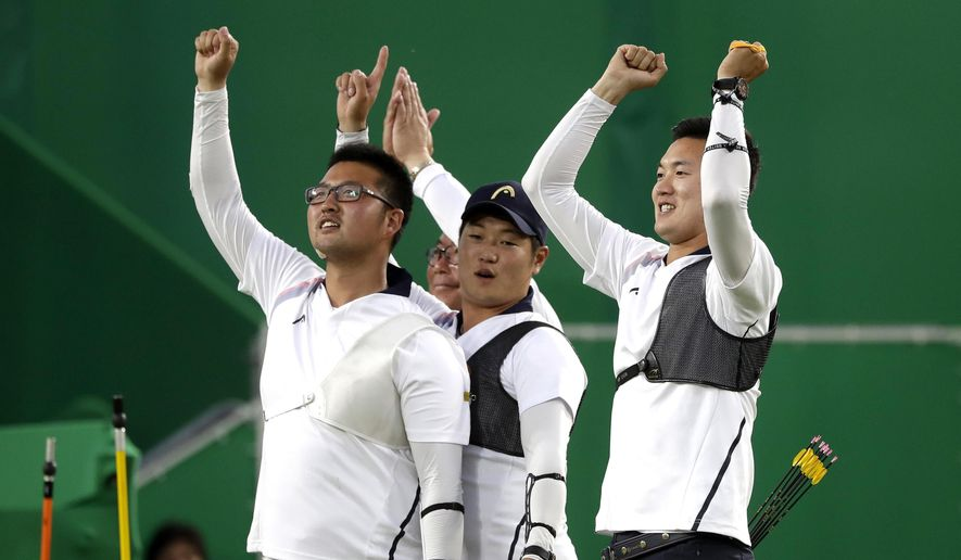 From left South Korea's Kim Woo-jin, Lee Seung-yun, and Ku Bon-chan, celebrate after winning the men's team archery gold medal match at the Sambadrome venue during the 2016 Summer Olympics in Rio de Janeiro, Brazil, Saturday, Aug. 6, 2016. (AP Photo/Alessandra Tarantino)