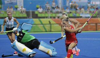 United States' Katie Bam, right, plays the ball against Argentina's goalkeeper Belem Succi, left, during a women's field hockey match at 2016 Summer Olympics in Rio de Janeiro, Brazil, Saturday, Aug. 6, 2016. (AP Photo/Hussein Malla)