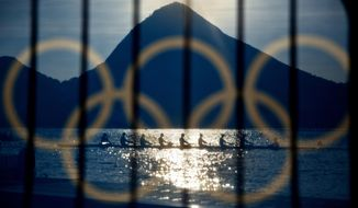Rowers are seen through a screen decorated with the Olympic rings as they practice at the rowing venue in Lagoa at the 2016 Summer Olympics in Rio de Janeiro, Brazil, Sunday, Aug. 7, 2016. (AP Photo/David Goldman)