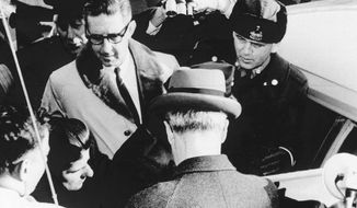 FILE - In this Feb. 26, 1967 black and white file photo, the crowd jeers self-confessed Boston Strangler Albert DeSalvo, lower left, as he is led outside the Lynn, Mass. police station. Casting is underway in summer 2016 for 'Stranglehold,' a new movie that will focus in part on a man who claimed psychic powers who helped investigators search for clues for nearly a dozen unsolved murders of women in the 1960s. (AP Photo, File)