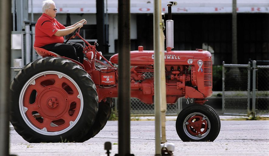 In this Thursday, Aug. 4, 2016 photo, Mike Hall drive a antique International Harvester Model C tractor near the horse barns at the Illinois State Fair in Springfield, Ill. The Illinois state budget mess has come home to roost at the Illinois State Fair, where admission is up 40 percent and for the first time, attending the Aug. 11 preview night is no longer free. (AP Photo/Seth Perlman)