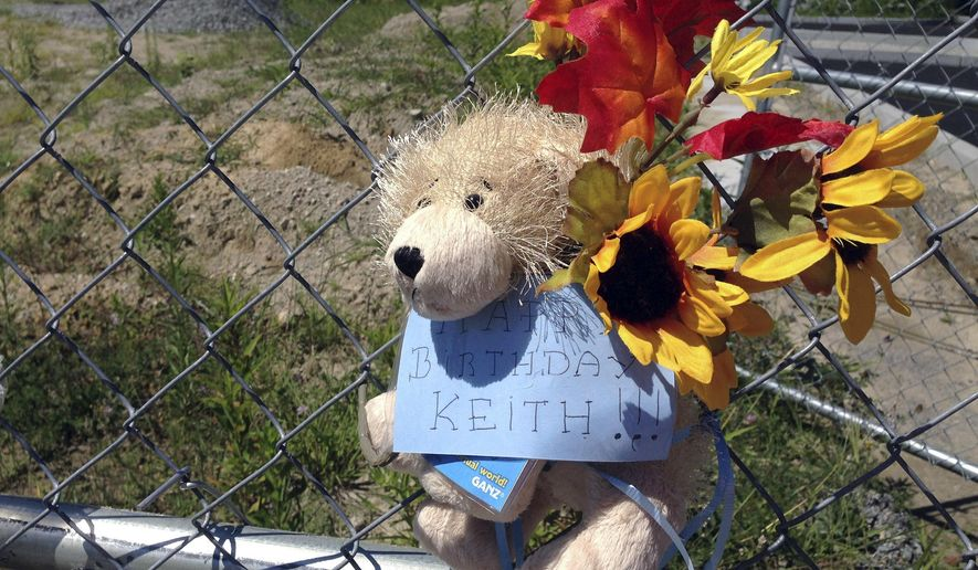 In this Thursday, Aug. 4, 2016 photo, a stuffed animal hangs from a chain link fence that surrounds the site of a 2003 nightclub fire that killed 100 people in West Warwick, R.I.  The memorial to mark the site of the nightclub fire in Rhode Island is nearing completion, and organizers say it has raised more than $1.9 million out of the $2 million it needs to build it and maintain it in perpetuity.  (AP Photo/Michelle R. Smith)