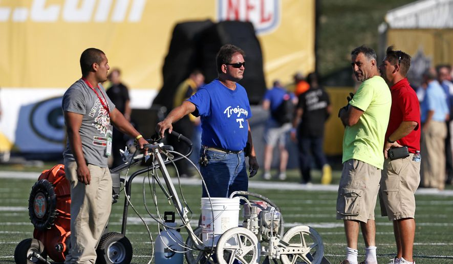 The ground crew at Tom Benson Hall of Fame Stadium check the turf after scraping the painted logo off the center of the field before an NFL preseason football game between the Green Bay Packers and the Indianapolis Colts, Sunday, Aug. 7, 2016, in Canton, Ohio. (AP Photo/Ron Schwane)