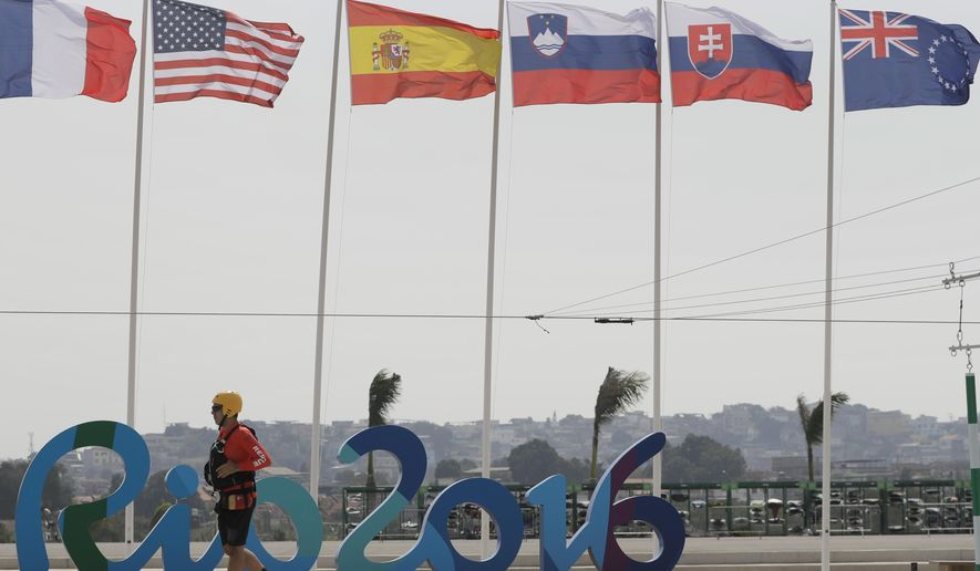 Flags are blown as wind delayed the start of the canoe single C1 men's heats of the Canoe Slalom at the 2016 Summer Olympics in Rio de Janeiro, Brazil, Sunday, Aug. 7, 2016. (AP Photo/Kirsty Wigglesworth)