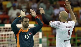 Qatar's Goran Stojanovic, left, and Qatar's Marko Bagaric celebrate after winning the men's preliminary handball match between Qatar and Croatia at the 2016 Summer Olympics in Rio de Janeiro, Brazil, Sunday, Aug. 7, 2016. (AP Photo/Ben Curtis)