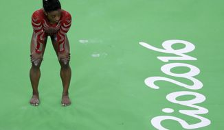 FILE- In this Aug. 4, 2016 file photo United States' Simone Biles waits her turn to train on the beam ahead of the 2016 Summer Olympics in Rio de Janeiro, Brazil. It shouldn't come as a surprise that some of the best-recognized names on the U.S. Olympic team belong to women. Biles is one of a record 292 women on the U.S. Olympic team. She could win up to five gold medals. (AP Photo/Julio Cortez, File)