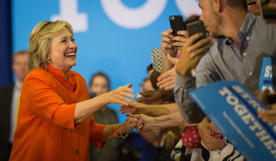 Democratic presidential candidate Hillary Clinton greets supporters before taking the stage for a campaign rally at The Coliseum in St. Petersburg, Fla., on Monday, Aug. 8, 2016. (Loren Elliott/Tampa Bay Times via AP)