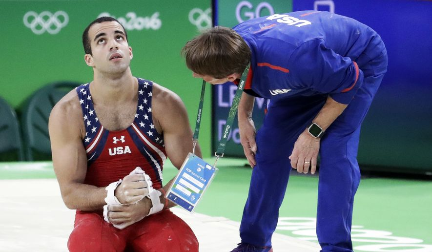 United States' Danell Leyva is checked by a team official after falling while performing on the horizontal bar during the artistic gymnastics men's team final at the 2016 Summer Olympics in Rio de Janeiro, Brazil, Monday, Aug. 8, 2016. (AP Photo/Dmitri Lovetsky)