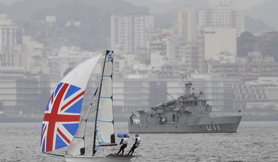 Sailors Charlotte Dobson and Sophie Ainsworth of Great Britain sail past a Brazilian navy ship in their 49erFX sailboat during a sailing training session of the 2016 Summer Olympics in Rio de Janeiro, Brazil, Sunday, Aug. 7, 2016. (AP Photo/Gregory Bull)