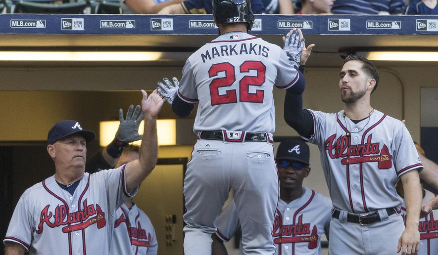 Atlanta Braves' Nick Markakis is greeted by teammates at the dugout after he hit a solo home run to right off of Milwaukee Brewers' Zach Davies during the second inning of a baseball game, Monday, Aug. 8, 2016, in Milwaukee. (AP Photo/Tom Lynn)