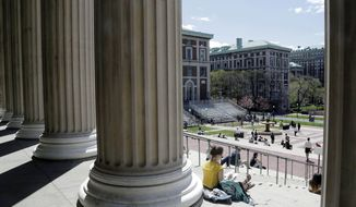 Students sit on the steps of Columbia University's Low Memorial Library in New York on April 29, 2015. (Associated Press) **FILE**