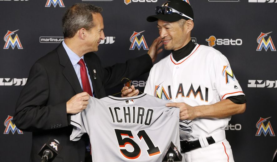 Jeff Idelson, left, president of the National Baseball Hall of Fame and Museum, and Miami Marlins' Ichiro Suzuki smile as Suzuki gives Idelson items from his 3,000 major league hit during a news conference, Monday, Aug. 8, 2016, in Miami. (AP Photo/Wilfredo Lee)