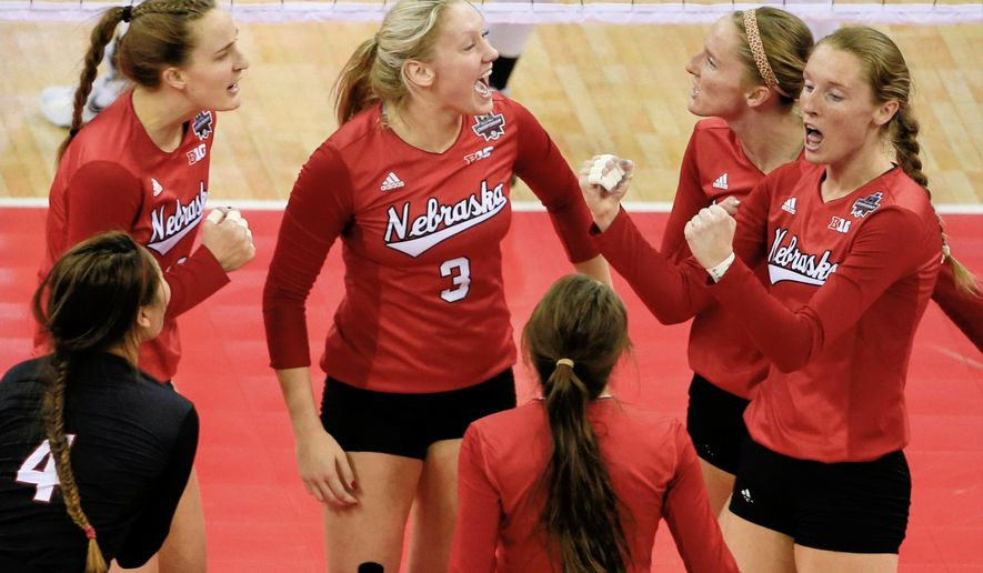 FILE- In this Dec. 19, 2015, file photo, Nebraska players including outside hitter Kadie Rolfzen, right, her twin sister middle blocker Amber Rolfzen, second right, libero Justine Wong-Orantes (4) and setter Kelly Hunter (3), celebrate a point against Texas during the NCAA women's volleyball tournament finals in Omaha, Neb. During Media Day on Monday, Aug. 8, 2016, Nebraska coach John Cook and his players are expected to discuss their hopes of winning a second straight national championship. (AP Photo/Nati Harnik, File)