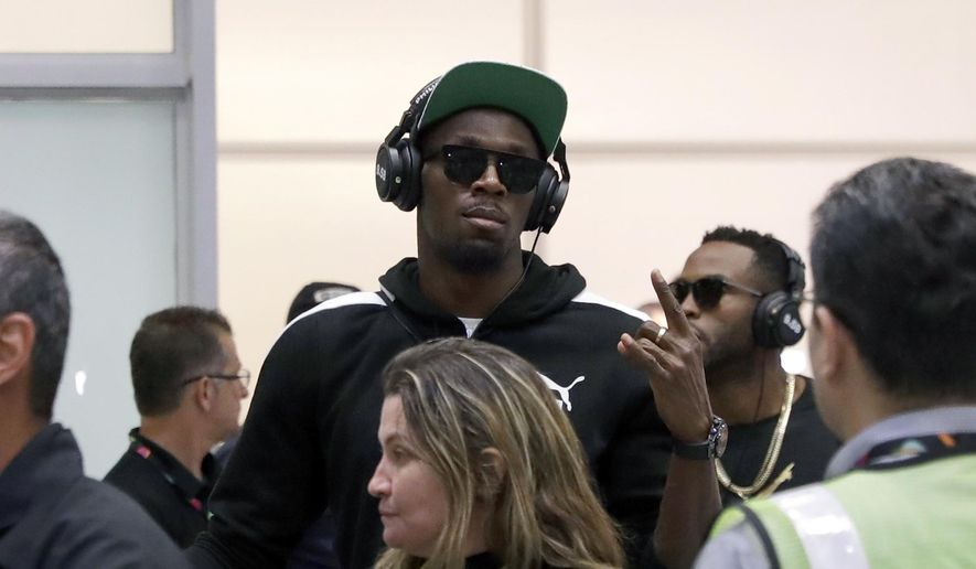 FILE - In this July 27, 2016 file photo, Jamaican Olympic runner Usain Bolt, center, gestures while arriving at Rio de Janeiro International Airport in Rio de Janeiro, Brazil. Bolt made his first major appearance Monday, Aug. 8 in Rio de Janeiro leading up to the Olympics, talking about his desire to break 19 seconds in the 200 meters, then ending his engaging news conference by boogieing offstage, accompanied by more than a dozen near-naked Samba dancers. (AP Photo/Patrick Semansky, File)