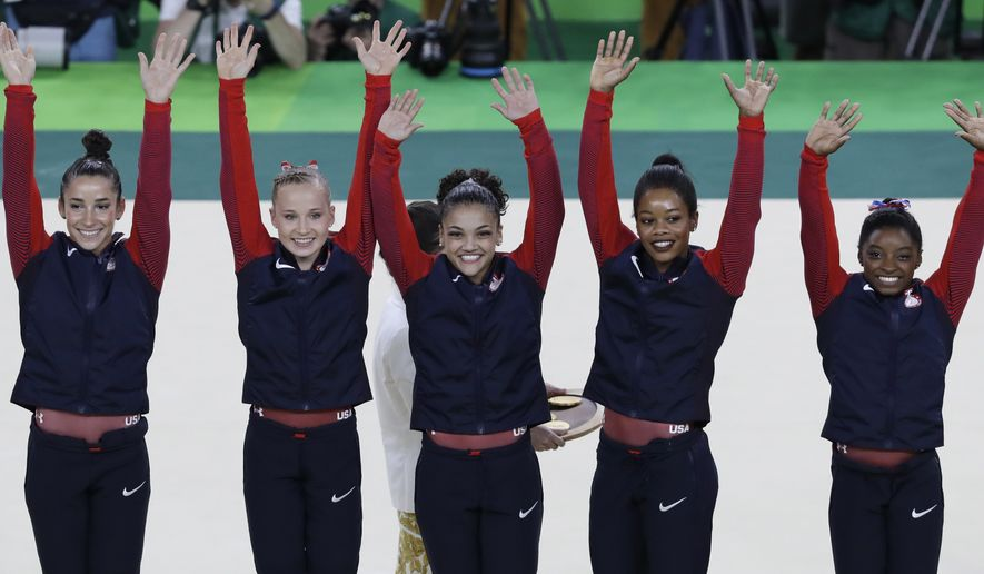 U.S. gymnasts and gold medallists, right to left, Simone Biles, Gabrielle Douglas, Lauren Hernandez, Madison Kocian and Aly Raisman raise their hands during the medal ceremony for the artistic gymnastics women's team at the 2016 Summer Olympics in Rio de Janeiro, Brazil, Tuesday, Aug. 9, 2016.(AP Photo/Rebecca Blackwell)