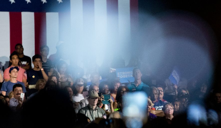 In this Aug. 8, 2016, photo, Seddique Mateen, the father of Omar Mateen, the Orlando gay nightclub shooter, far left at bottom, take a photograph with his phone as Democratic presidential candidate Hillary Clinton, right, speaks at a rally at Osceola Heritage Park, in Kissimmee, Fla., Monday, Aug. 8, 2016. (AP Photo/Andrew Harnik)