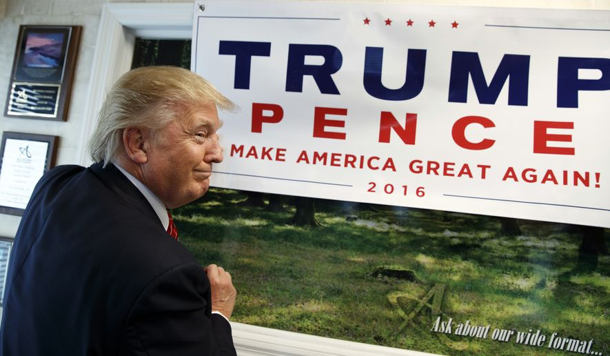 Republican presidential candidate Donald Trump autographs a banner during a visit to Allegra Print and Imaging, Tuesday, Aug. 9, 2016, in Fayetteville, N.C. (AP Photo/Evan Vucci)