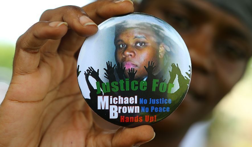 "FILE - In this Aug. 21, 2014 file photo, Nikki Jones, of Spanish Lake, Mo, holds a button in support of Michael Brown while visiting the community in the apartment development near where he was fatally shot in Ferguson, Mo.  Brown's death ""opened the eyes of the world"" to concerns about law enforcement's treatment of black people, Brown's father said Tuesday, Aug. 9, 2016,  during a memorial service marking the two-year anniversary of the shooting. (Curtis Compton/Atlanta Journal-Constitution via AP, File)"