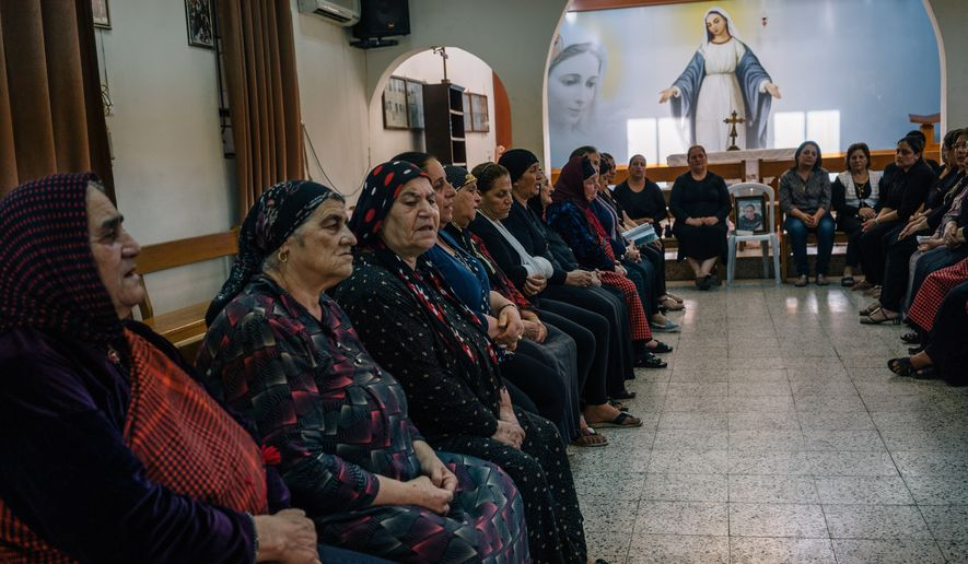 In this Monday, Aug. 8, 2016, photo, Christian women gather at an Assyrian church in Irbil, Iraq, to mourn the death of a member of their community who died in Europe. As operations to retake the militant-held city of Mosul ramp up, Iraqi Christians displaced from the area by the Islamic State group say even a military defeat of the extremists in Iraq, will not make the country safe for minorities again. (AP Photo/Alice Martins) ** FILE **