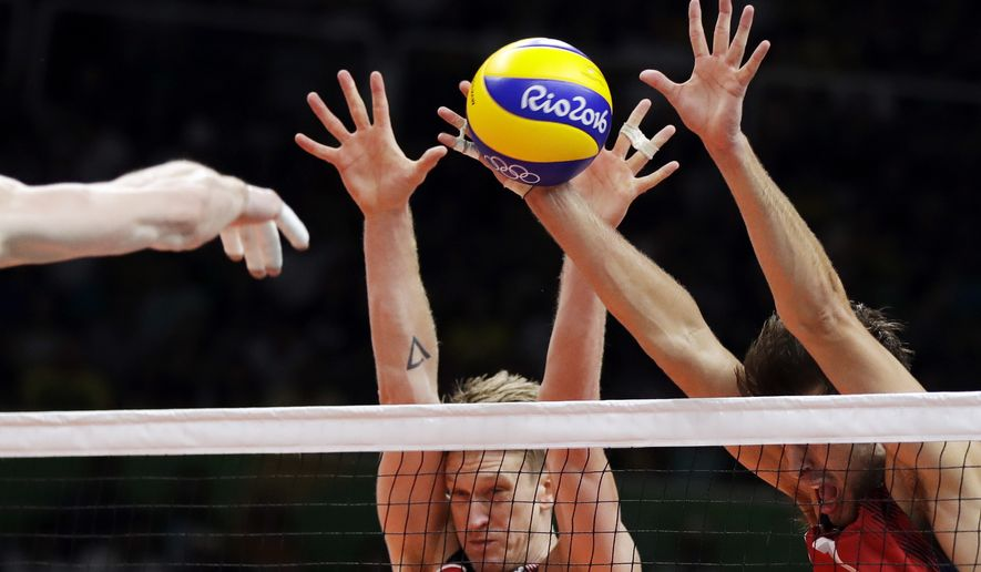 Italy's Ivan Zaytsev, left, spikes the ball as United States' Maxwell Holt, center, and Aaron Russell block during a men's preliminary volleyball match at the 2016 Summer Olympics in Rio de Janeiro, Brazil, Tuesday, Aug. 9, 2016. (AP Photo/Matt Rourke)