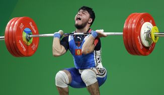 Izzat Artykov, of Kyrgystan, competes in the men's 69kg weightlifting competition at the 2016 Summer Olympics in Rio de Janeiro, Brazil, Tuesday, Aug. 9, 2016. (AP Photo/Mike Groll)