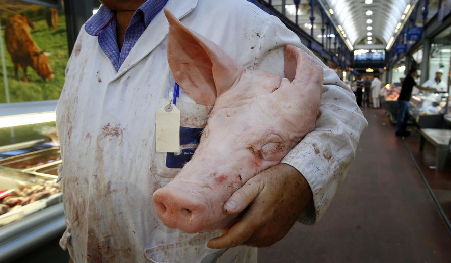 In this photo taken on Monday, July 18, 2016, a butcher carries a pigs head at Smithfield Market in London. Welsh farmers like Rees Roberts, who have 1,000 acres with sheep, cattle and crops, can expect to earn a premium on their meats thanks to a certificate of regional authenticity. But that marker of distinction _ the same kind that ensures Champagne can only come from the French region of the same name _ is granted by the European Union and is now at risk after Britain voted to leave the 28-country bloc. (AP Photo/Kirsty Wigglesworth)