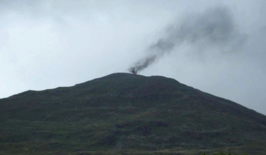 In this image provided by The National Trust, a thick plume of smoke rises from Yr Aran, a peak in the Snowdonia mountain range after a helicopter made an emergency landing in north Wales, Tuesday Aug. 9, 2016.  Britain's defense ministry says a Royal Air Force training helicopter made an emergency landing on a mountain peak in Wales and then burst into flames, after developing a technical fault.  All four people aboard the helicopter escaped safely. (The National Trust via AP)