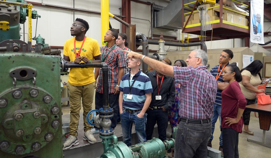 Mike Tucker with Eastman Chemical Co. talks to a group of pre-apprenticeship program students from Workforce Solutions about a compressor in Eastman's safety training facility during a tour Tuesday, Aug.  2, 2016, in Longview, Texas. (Les Hassell/The News-Journal via AP)