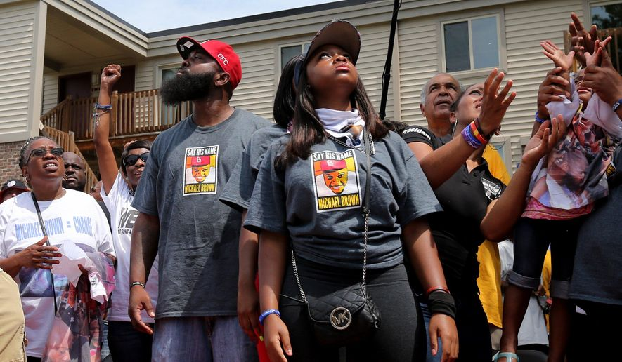 Michael Brown, Sr., center, watches as white doves fly away after 4.5 minutes of silence during a memorial ceremony for Brown's son Michael Brown on Canfield Drive in Ferguson, Mo.,  Tuesday, Aug. 9, 2016. August 9 marks the second anniversary of Brown's fatal shooting by Ferguson police officer Darren Wilson. Brown's death sparked local protests that spread around the world and breathed live into the Black Lives Matter movement. A St. Louis County grand jury and an investigation by the Department of Justice found that Wilson was justified in shooting Michael Brown. (David Carson/St. Louis Post-Dispatch via AP)