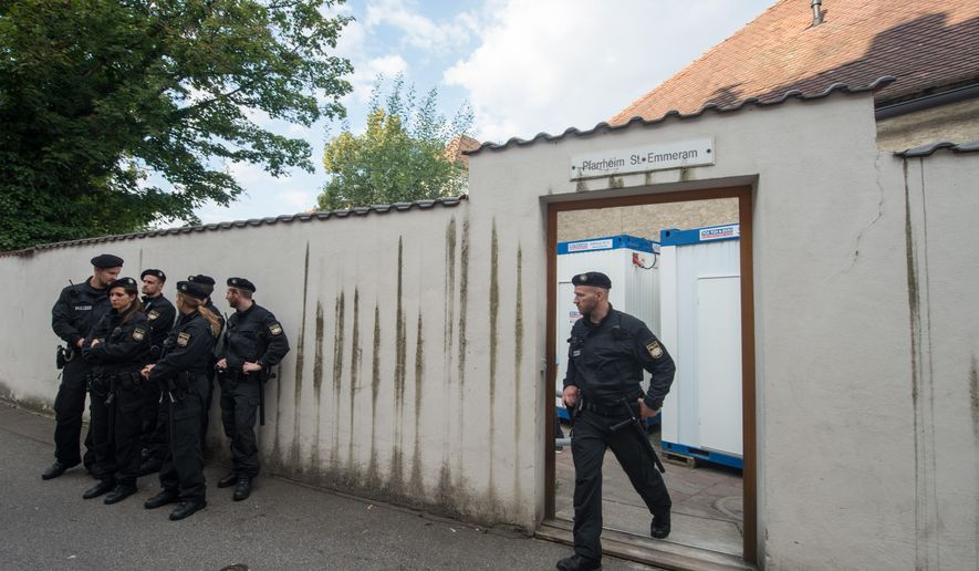 In this Aug. 8, 2016 picture police officers standing in front of the parish hall of St. Emmeram where refugees were living in Regensburg, Germany.The  Roman Catholic diocese in Bavaria says it has ended a five-week protest at a church building by migrants from the Balkans. Some 50 migrants started camping out at Regensburg Cathedral early last month, demanding the right to stay in Germany and protesting the Balkan nations' designation as safe countries. A few days later, most moved to a vicarage across town. The diocese  said the last 16 people were persuaded to leave Monday by police. (Armin Weigel/dpa via AP)