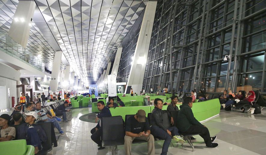 Passengers wait for their flights on the first day of operation of the new terminal of Soekarno-Hatta International Airport in Tangerang in the outskirt of Jakarta, Indonesia, early Tuesday, Aug. 9, 2016. The Indonesian capital's airport opened its $560 million, steel and glass Terminal 3 Tuesday after years of operating at far above its passenger capacity. (AP Photo/Tatan Syuflana)