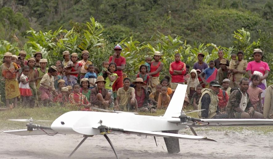 In this July 27, 2016 image made from a video provided by Vayu, Inc., residents from Ranomafana, Madagascar, watch before a drone containing medical samples takes off on a test flight from their remote village, which can only be reached on foot. Long Island's Stony Brook University, which has been working in the Indian Ocean island nation off eastern Africa for nearly three decades and maintains a research station there, has teamed with Michigan startup company Vayu, Inc. to ship laboratory samples via drone for analysis. Stony Brook officials say this is one of the first efforts involving the small unmanned aircraft that can land and takeoff. (Stony Brook University/Vayu Inc. via AP)